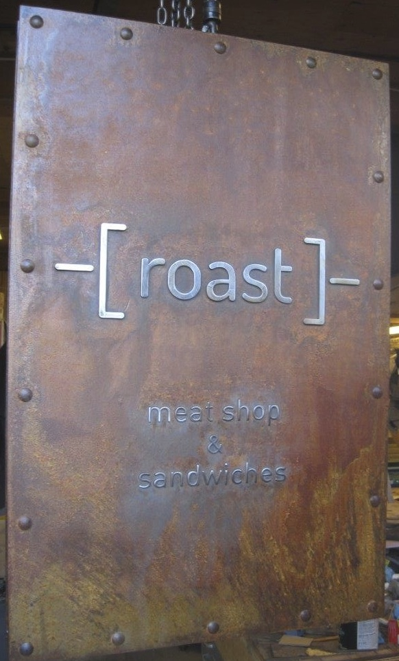 inlayed steel letters in a rustic metal sign